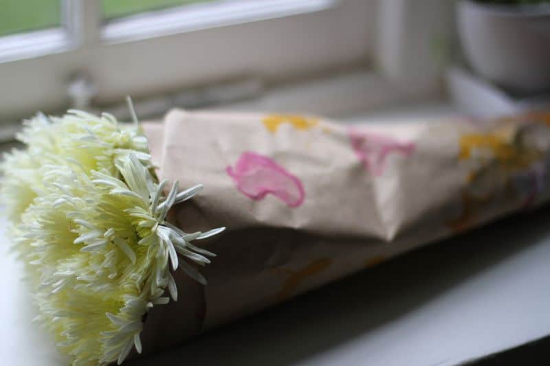 Homemade wrapping paper wrapped around a bouquet of flowers