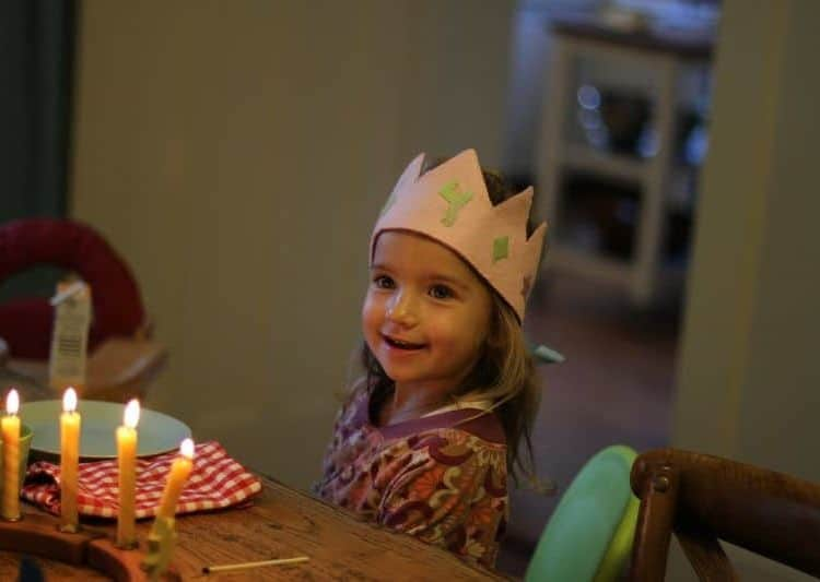 Little girl celebrated her birthday wearing a birthday crown with the number 4 on it.