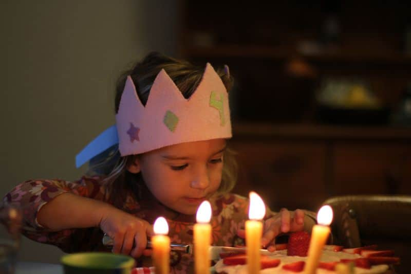 Little girl celebrated her birthday wearing a birthday crown and cutting a cake.
