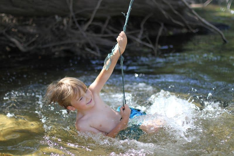 Child plays on rope swing in river