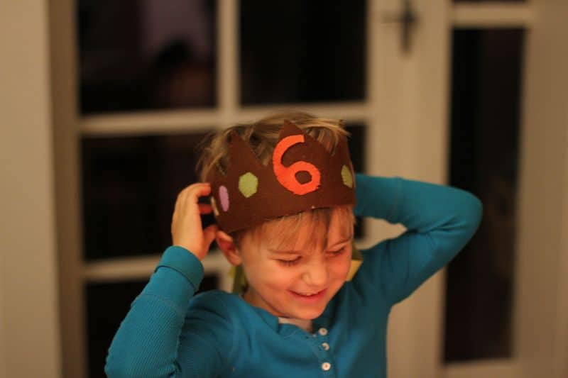 Little boy celebrates his birthday wearing a birthday crown with the number 6 on it.