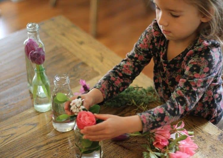 Young girl puts flowers in vases