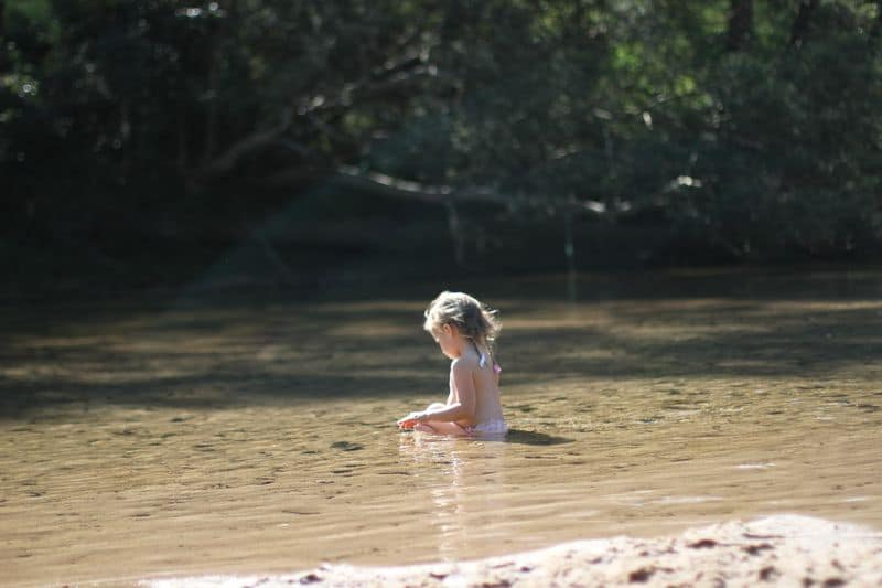 Young girl plays in a river