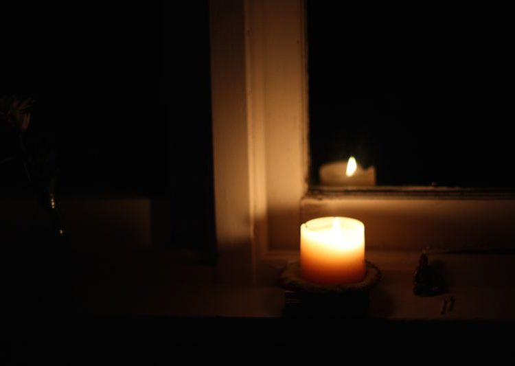 Candle on windowsill for early morning meditation
