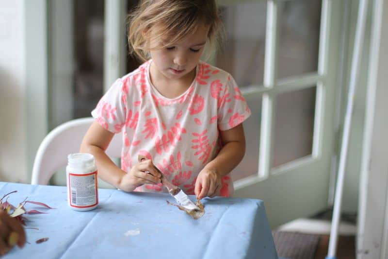 Little girl uses glue to start nature crafts