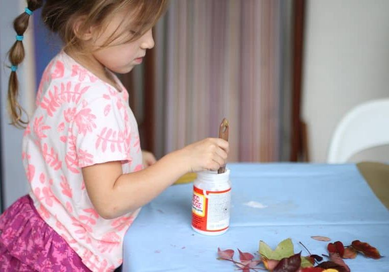 Little girl dips brush in glue for crafting-800wi